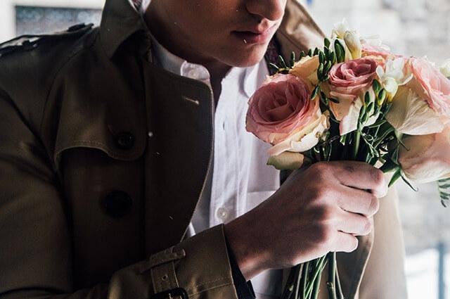 ファッショナブルなバラを持つ男性