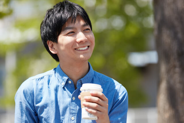 コーヒーを持って笑う男性