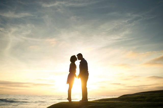 夕日をバックにキスをするカップル