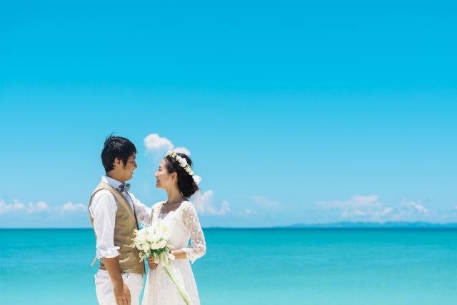青空と海を背景に向かい合うカップル