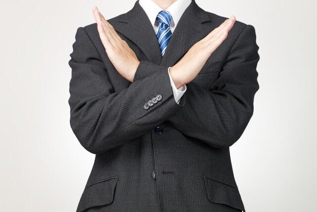 ×を出したスーツの男性