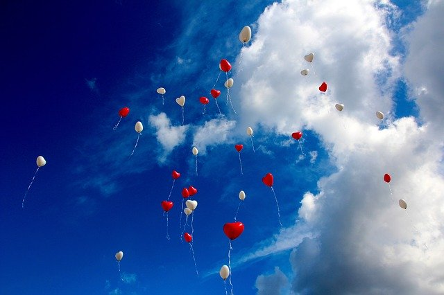 空に飛んでいくハートの風船