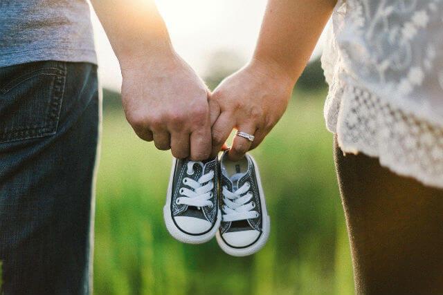 子供用の靴を持って繋がれている男女の手