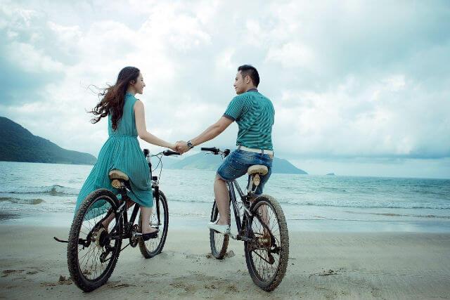 自転車に乗り手をつなぐカップル