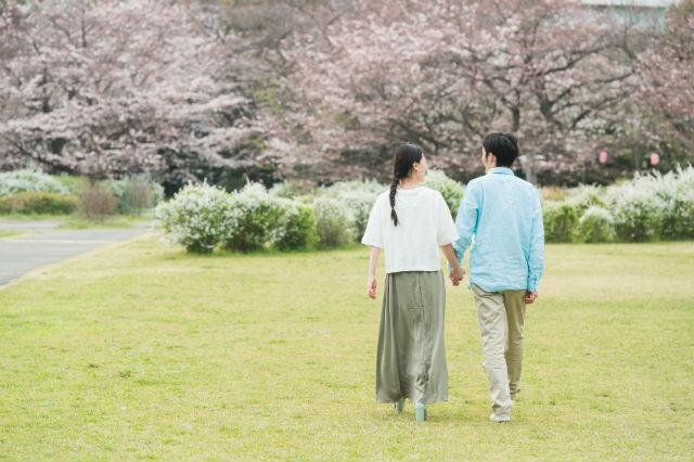 公園を歩くカップルの後ろ姿